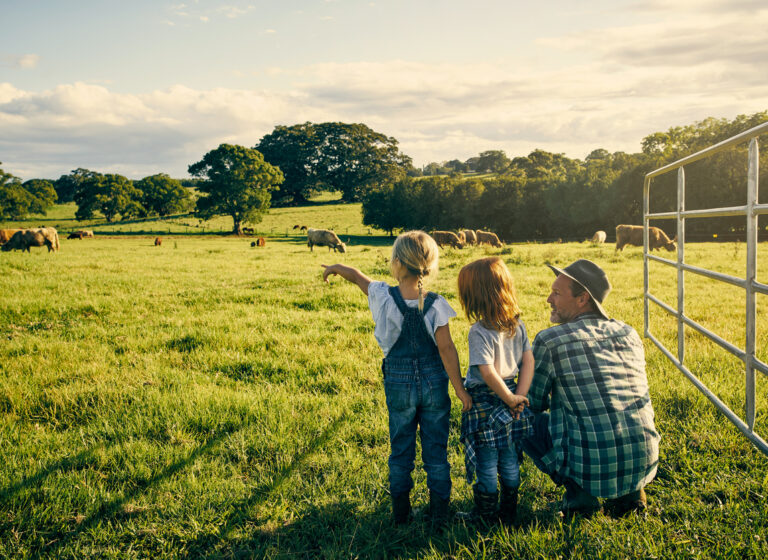 Young family of farmers observing their cows with a boy pointing.